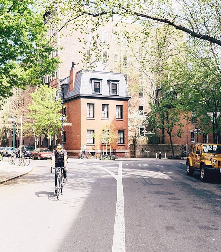 Man Wearing T Shirt Biking Down a Road that Forks Off with Small Brick Buildings Aligned with Trees